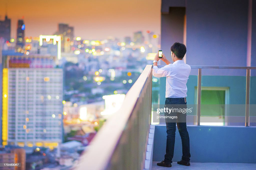 Young photographer with night light of big city