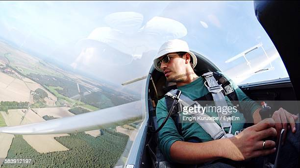 Young Pilot Flying Glider Airplane Over Landscape Against Sky