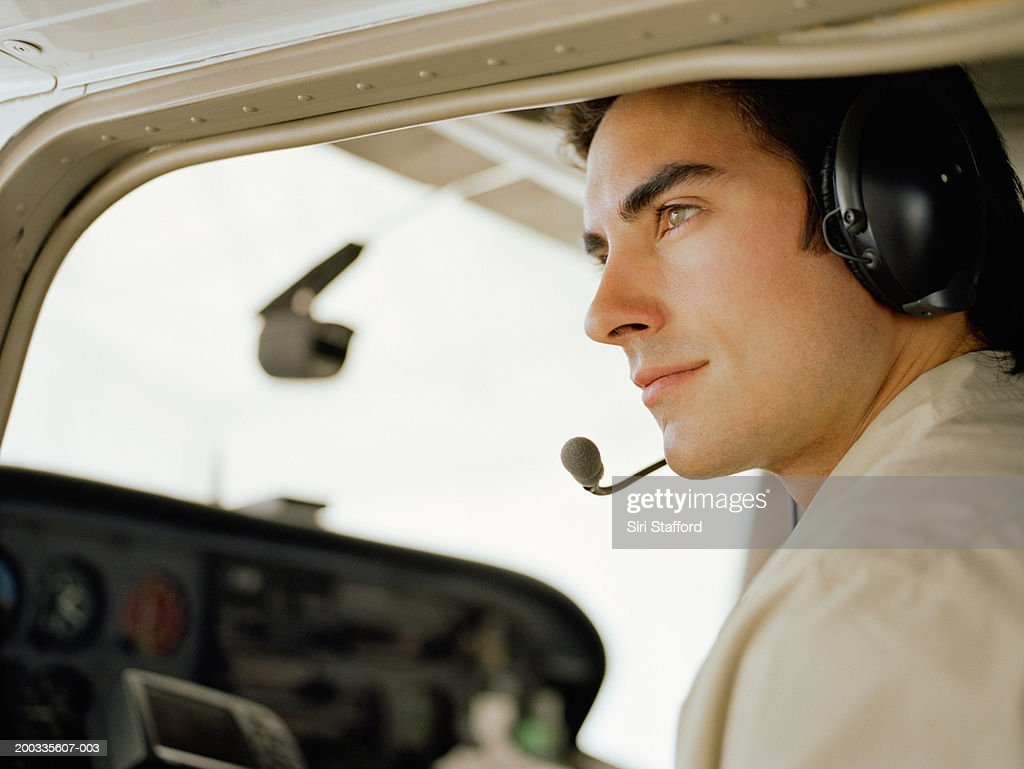 Young pilot sitting in cockpit of private plane, portrait