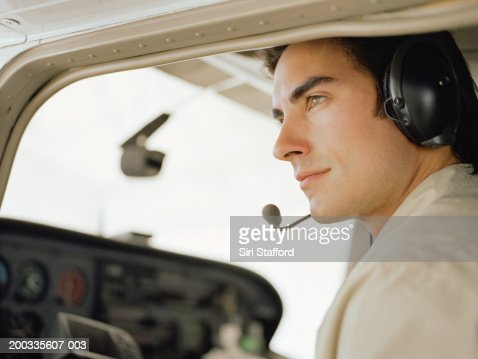 Young pilot sitting in cockpit of private plane, portrait : Stock Photo