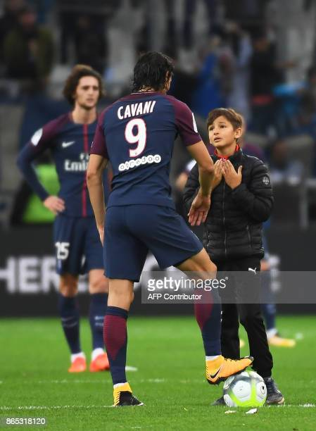 Young pitch invader talks to Paris SaintGermain's Uruguayan forward Edinson Cavani on October 22 2017 at the Velodrome stadium in Marseille southern...