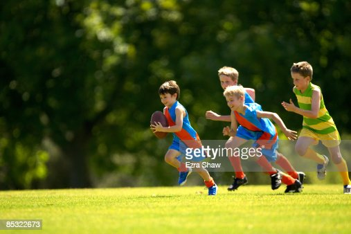 Young player running from opposition with ball : Foto stock