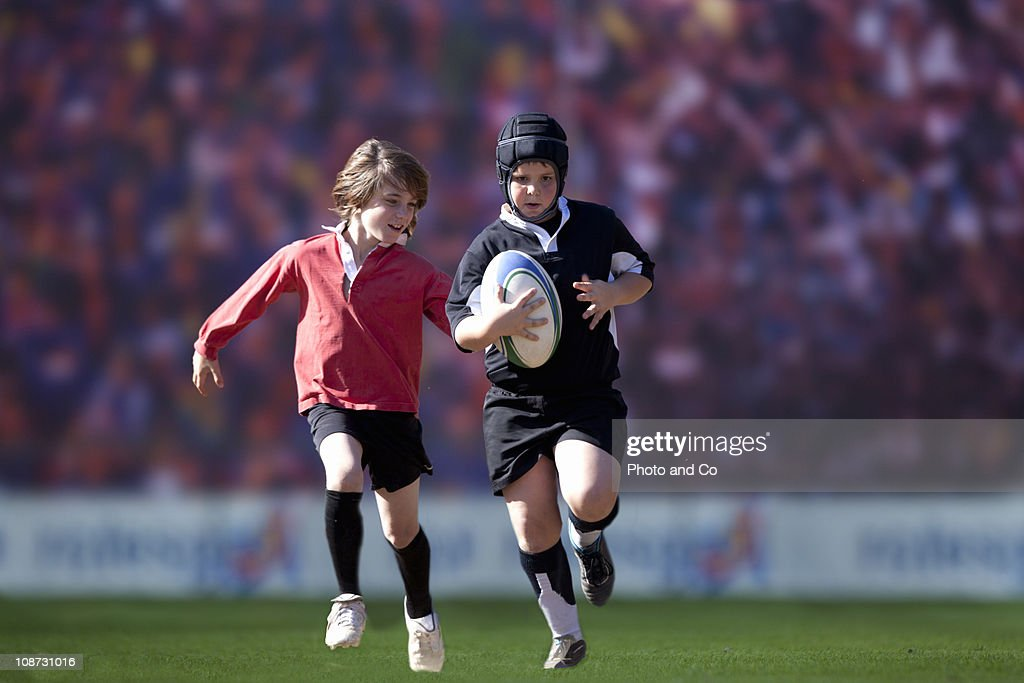 Young player running with ball pursued by opponent