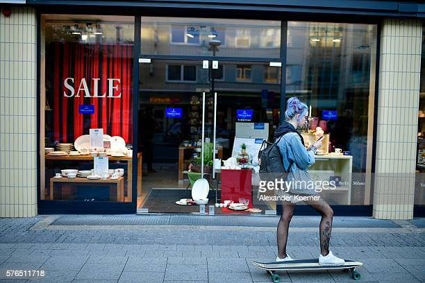 A young player stands on a longboard while chasing through the city centre of Hanover while holding her smartphone and playing 'Pokemon Go' on July...