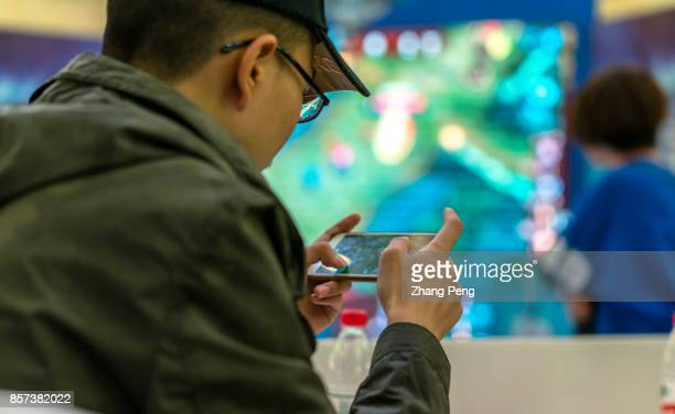Young players compete in a battle match of the mobile game Arena of Valor held in a shopping mall Arena of Valor 5v5 Arena Game China's most popular...