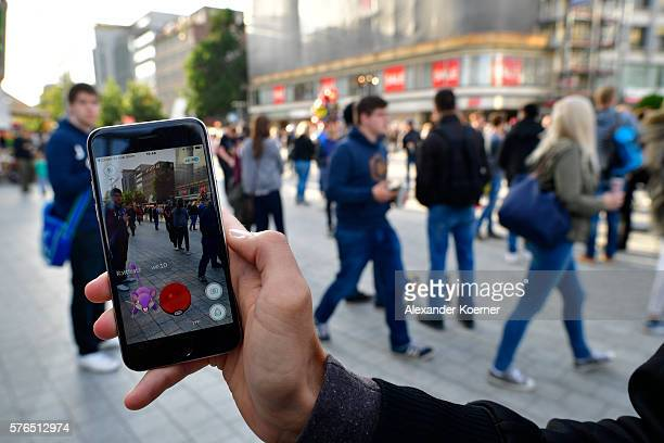 A young players holds his smartphone while playing 'Pokemon Go' on July 15 2016 in Hanover Germany 1200 players have participated in the night walk...