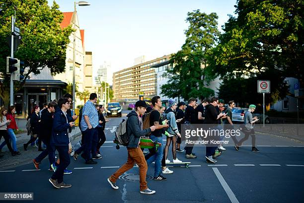 Young players walk through the city centre of Hanover while holding their smartphones and playing 'Pokemon Go' on July 15 2016 in Hanover Germany...