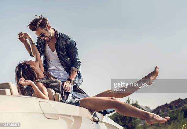 Jeune couple s'amuser ensemble espiègle en voiture décapotable.