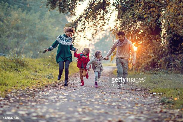 Young playful family having fun while running in the park.