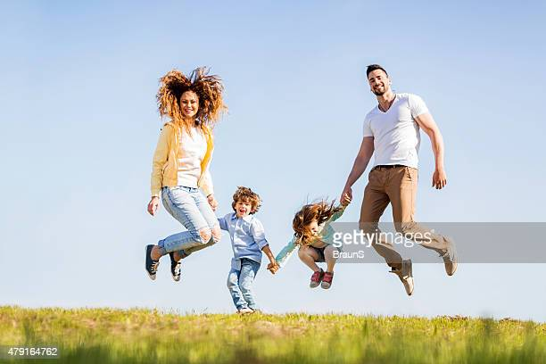 Young playful family jumping together in nature during spring day.