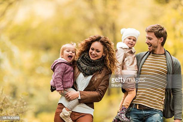 Young playful family taking a walk during autumn day.