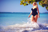 young plus size woman in swimwear enjoying vacation in water splash on the beach
