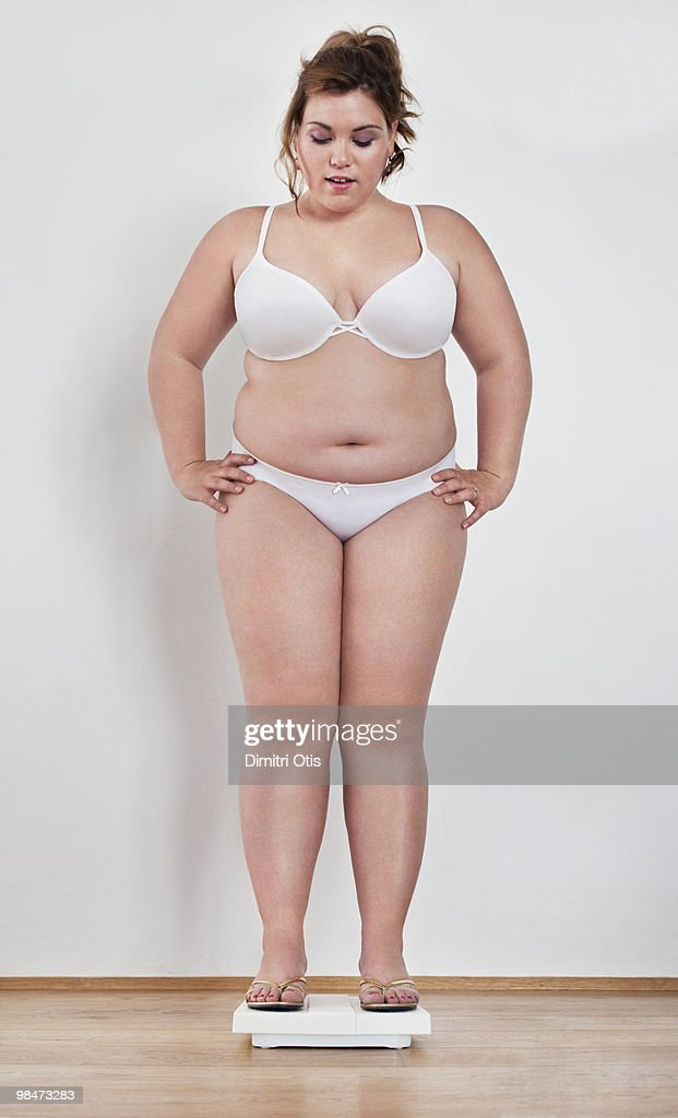Young plus-size woman on scale : Stock Photo