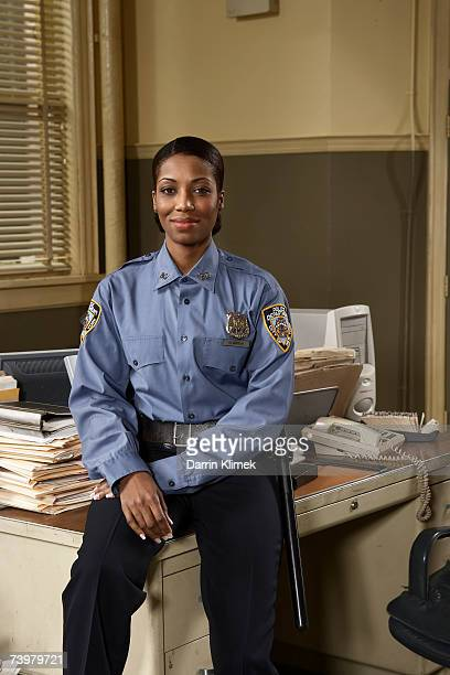 Young policewoman sitting on desk, smiling, portrait