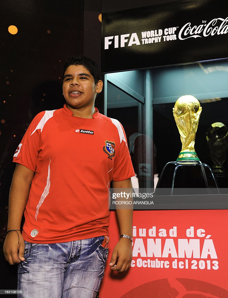 A young poses next to the FIFA World Cup in Panama City, on October 4, 2013. The Cup is in Panama for two days as part of a tour to exhibit it in 89 countries before the beginning of the FIFA World Cup Brazil 2014. AFP PHOTO/ Rodrigo ARANGUA