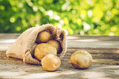 Young potatoes in a sack on a wooden table.
