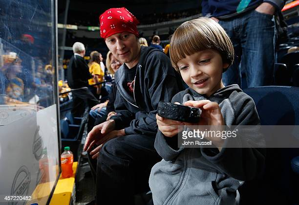 Young Predators fan Caleb Holcomb checks out his gift from goalie Carter Hutton of the Nashville Predators after warm ups against the Calgary Flames...
