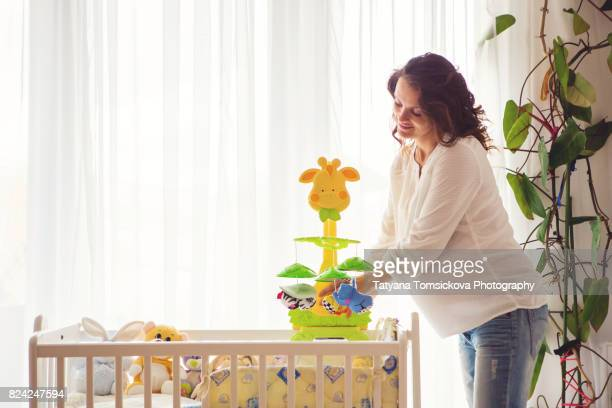 Young pregnant attractive woman, preparing baby bed for her newborn, beautiful back light