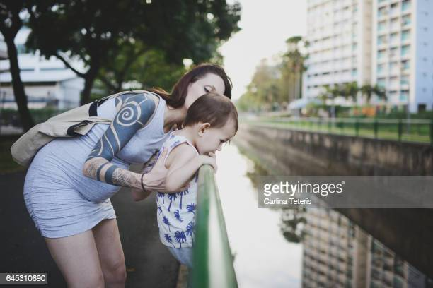 Young pregnant mom holding her son over a canal in a park