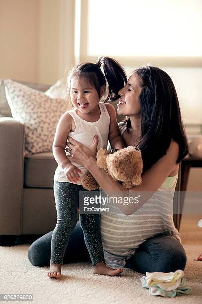 Young pregnant mother holding and laughing with her young daughter