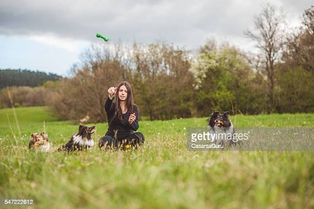 Young pregnant woman and her dogs outdoors