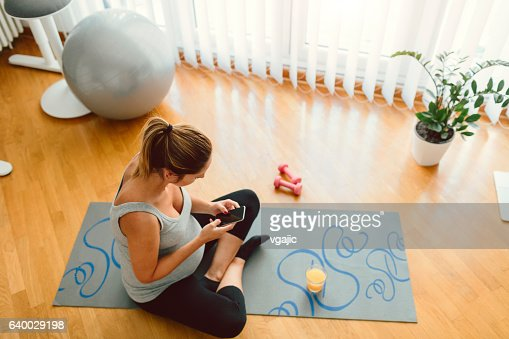 Young Pregnant Woman Exercise And Using Smart Phone At Home.