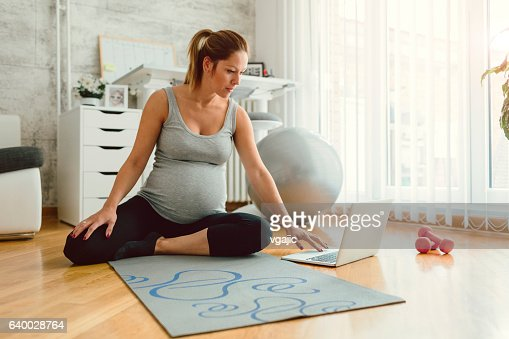 Young Pregnant Woman Exercises At Home.