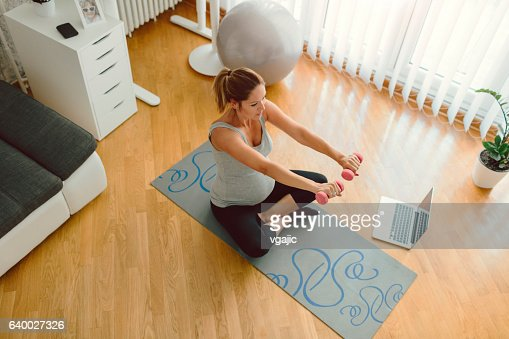 Young Pregnant Woman Exercising At Home