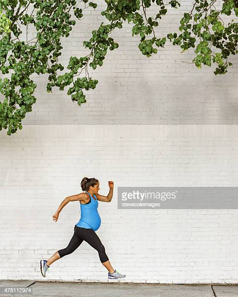 Young pregnant woman jogging down sidewalk in city.