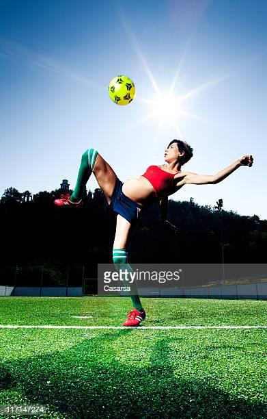 Jeune femme enceinte heureuse, jouer au football