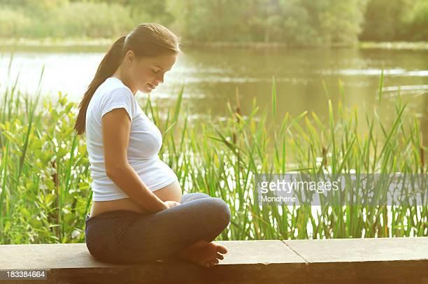 Jeune femme enceinte heureuse, se détendre dans un parc
