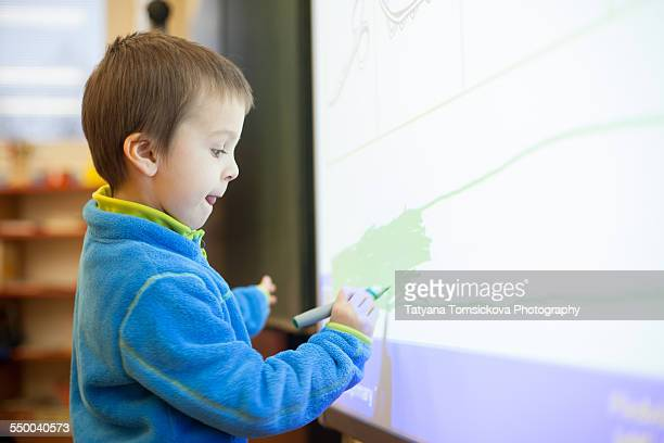 Young preschool boy, trying new touch pad screen