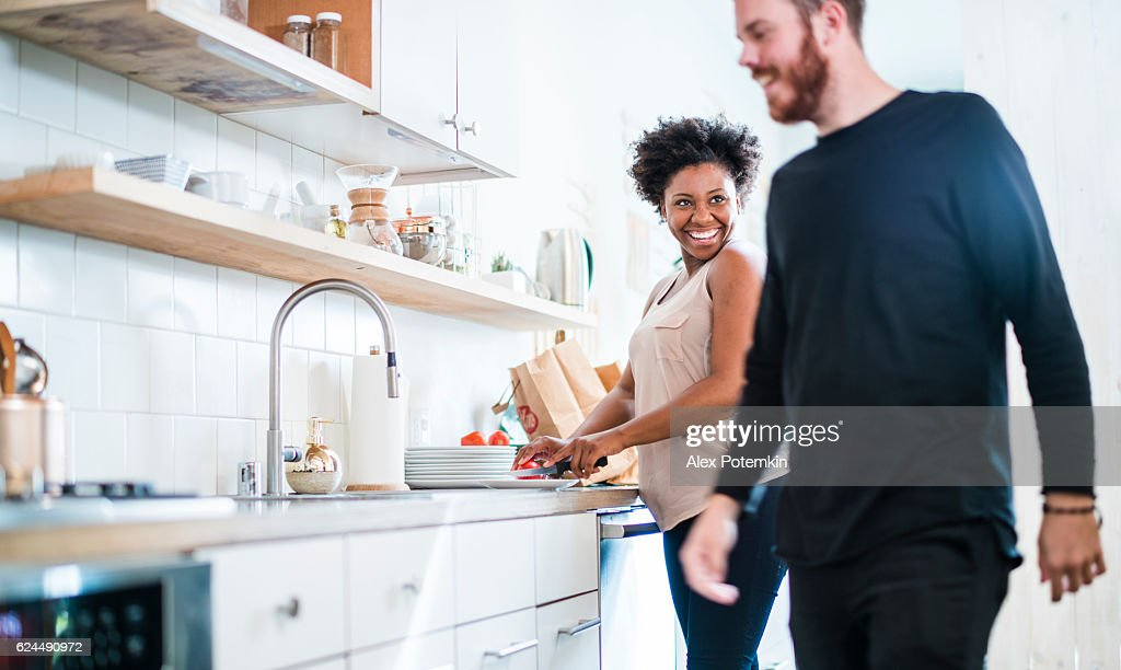 Young pretty black woman make soup in kitchen : Foto de stock