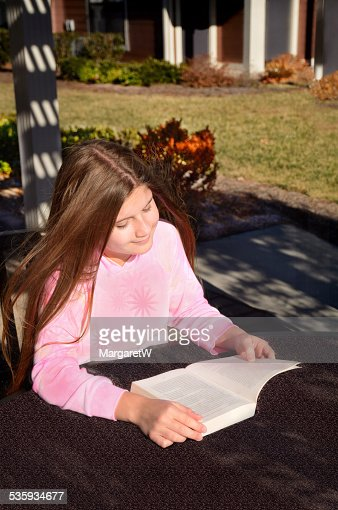 Young pretty girl reading a book outdoors. : Stock Photo