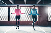 Shot of young shapely girls in sportswear training and skipping in gym against barred window.