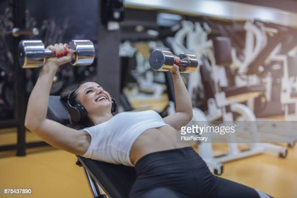 Mujer bonita joven haciendo ejercicios de pecho con pesas poco