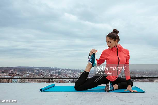 young pretty woman doing yoga stretching on the rooftop