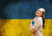 Portrait of beautiful young lady in glasses reading book over Ukrainian flag background