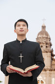 Young Priest Looking to Sky in Front Of Church