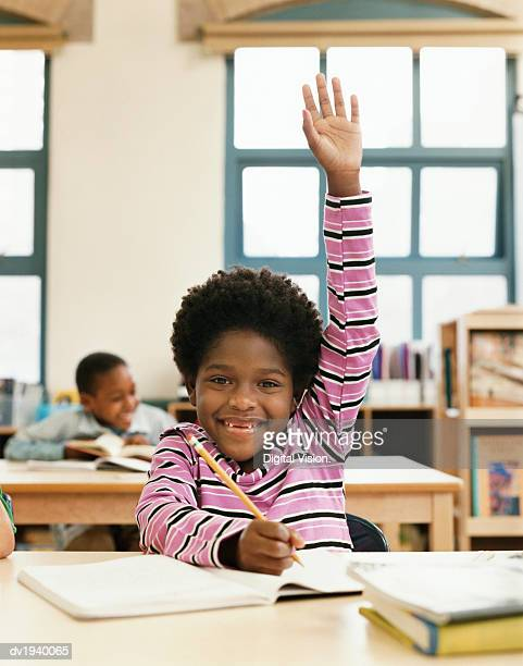 Young Primary Schoolboy With His Hand Raised in Classroom
