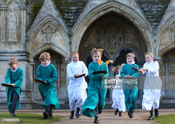 Young probationers the trainee choristers of Salisbury Cathedral Choir flip pancakes to mark Shrove Tuesday outside the West Front of the 13th...