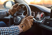 Young person driver in leather gloves travelling in luxury car on sunrise inside view with dashboard, speedometer and gps navigation hands close-up shop