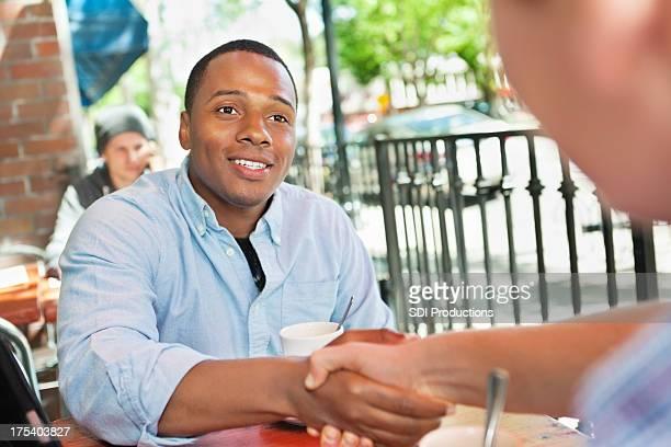 Jeune professionnel homme accueillant un collègue ou à un ami au café