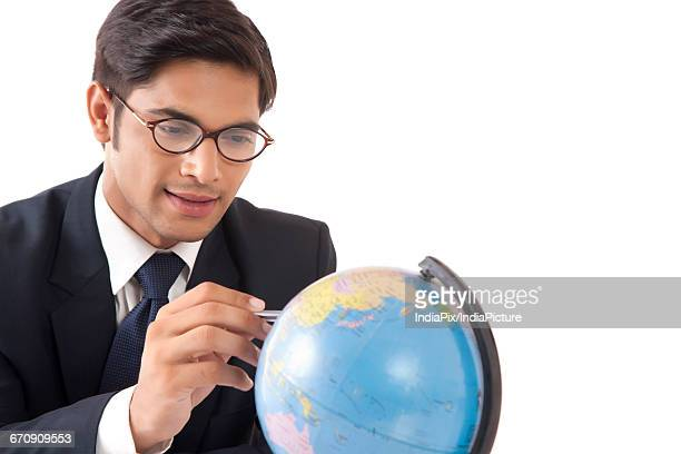 Young professional man locating countries on globe against white background