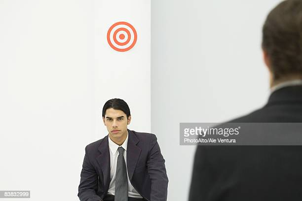 Young professional man sitting below bull's-eye, boss standing in foreground