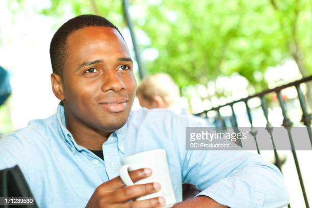Young professional man with coffee and tablet at outdoor cafe