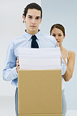 Young professional with documents stacked on cardboard box, woman standing behind him with her hand on his shoulder, both looking at camera