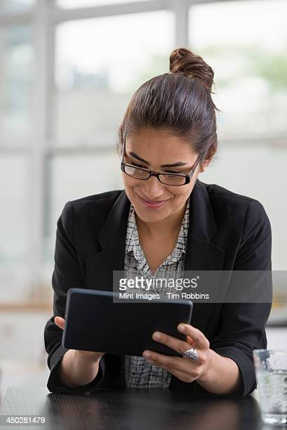 Young professionals at work. A woman wearing a black jacket, using a black digital tablet.