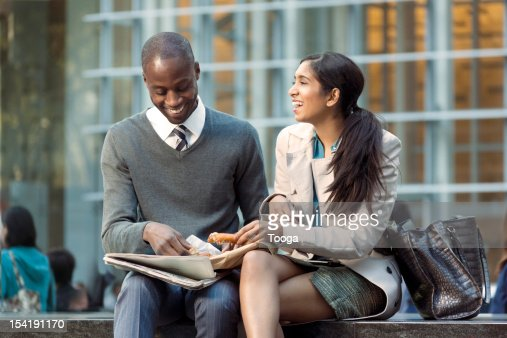 Young professionals sharing a snack and a laugh : Stock Photo