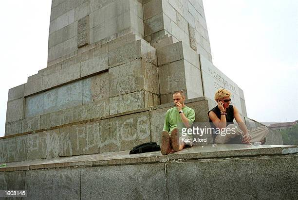 Young professionals smoke marijuana and talk on mobile phones August 8 2001 in Sofia Bulgaria while sitting at a monument overlooking a communistera...